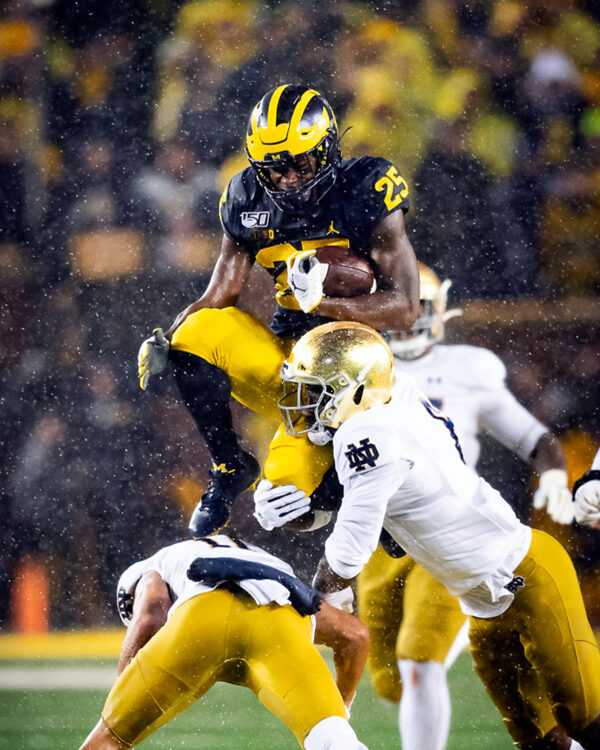 Michigan running back Hassan Haskins hurdles over a charging Notre Dame player
